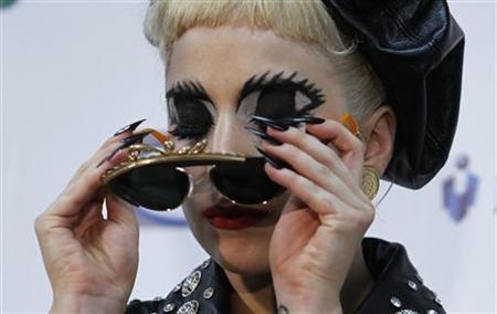 Lady Gaga takes off her sunglass during a news conference after performing at the MTV Video Music Aid Japan in Chiba, near Tokyo, June 25, 2011. REUTERS/Toru Hanai