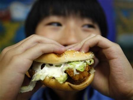 A boy poses with a chicken burger at a fast food outlet in Taipei January 29, 2010. REUTERS/Nicky Loh