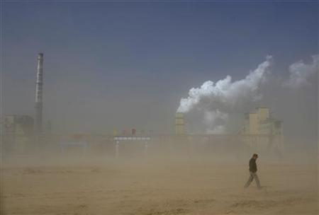 A man walks past a coal plant amidst a dust storm in Lingwu, Ningxia Hui Autonomous Region March 29, 2011. REUTERS/Stringer