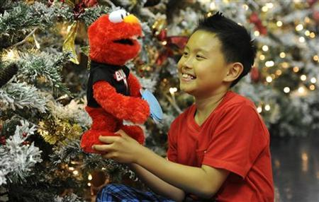Rio Nguyen, 8, poses for photographers at Hamleys toy store with a Sesame Street Elmo doll in London June 28, 2011. REUTERS/Paul Hackett