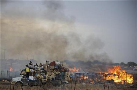 A truck piled with furniture and other items drives past burning businesses and homesteads, locally known as ''tukuls'', burn in the centre of Abyei, central Sudan in this handout photograph released on May 28, 2011. REUTERS/Stuart Price/United Nations Mission in Sudan/Handout