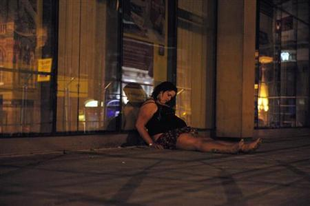 A woman lies on the street during a night out in Newcastle, northern England May 3, 2009. REUTERS/Nigel Roddis