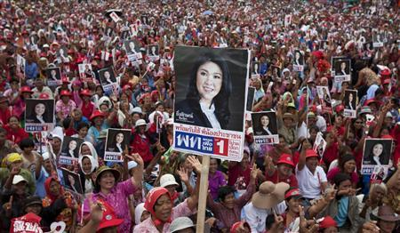 Supporters of Yingluck Shinawatra, the sister of former Thai Prime Minister Thaksin Shinawatra, raise her image as she took stage during a campaign rally in Si Saket north east Thailand on June 29, 2011. Thailand will hold a general election on July 3. REUTERS/Adrees Latif
