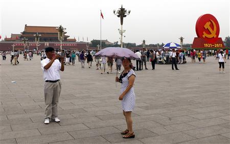 A giant Communist emblem is seen on display as a woman holding an umbrella poses for a photograph at Beijing's Tiananmen Square June 30, 2011. REUTERS/Stringer