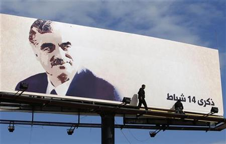 Workers adjust a giant billboard of Lebanon's assassinated former prime minister Rafik al-Hariri at Sidon, southern Lebanon, February 13, 2011. REUTERS/Ali Hashisho