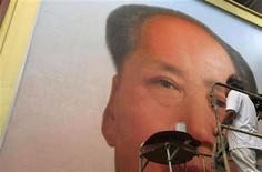 <p>Ge Xiaoguang wipes off extra paint on a giant portrait of China's late Chairman Maozedong in his working studio located between the Tiananmen Square and the Forbidden City in Beijing, June 29, 2011. REUTERS/Barry Huang</p>