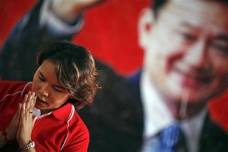 A woman prays in front of a picture of ousted Thai premier Thaksin Shinawatra during a religious ceremony at a temple in the village of Suan Mon near Udon Thani in northeastern Thailand June 25, 2011. REUTERS/Damir Sagolj