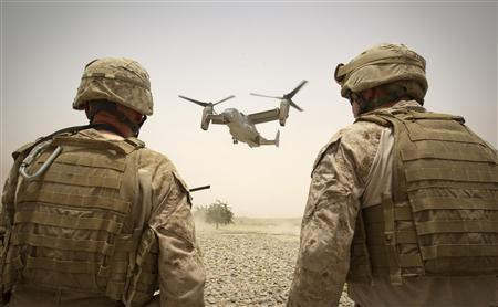 U.S. Marines of Weapons Company, 1st Battalion, 3rd Marines watch a V-22 Osprey aircraft as its lands at the Camp Gorgak in Helmand province, southern Afghanistan, June 30, 2011. REUTERS/Shamil Zhumatov