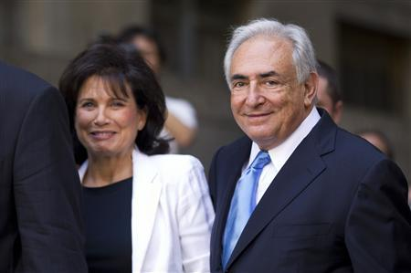 Former IMF chief Dominique Strauss-Kahn smiles as he and his wife Anne Sinclair depart a hearing at the New York State Supreme Courthouse in New York July 1, 2011. REUTERS/Lucas Jackson