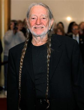 Singer Willie Nelson poses for photographers on the red carpet as he arrives to pay tribute to comedian, actor, author and musician Bill Cosby, who is being awarded the Kennedy Center for the performing Arts' Mark Twain Prize for American Humor, in Washington, October 26, 2009. REUTERS/Mike Theiler