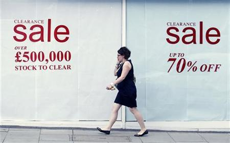 A woman passes a shop with a clearance sale in Chelsea in west London June 29, 2011. REUTERS/Luke MacGregor