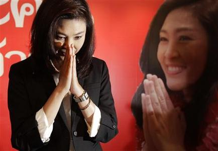 Yingluck Shinawatra, sister of ousted premier Thaksin Shinawatra, greets reporters and supporters gathered at her party's headquarters after voting in general elections ended in Bangkok July 3, 2011. REUTERS/Damir Sagolj