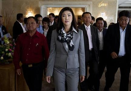 Puea Thai Party's Yingluck Shinawatra (C) arrives to attend a news conference on the formation of her coalition in Bangkok July 4, 2011. Yingluck on Monday announced the formation of a five-party coalition led by her Puea Thai Party, a day after her stunning election victory, which will control about 60 percent of parliament. REUTERS/Sukree Sukplang