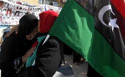<p>Libyan women cry and celebrate with a Kingdom of Libya flag after receiving news of an arrest warrant issued against Libyan leader Muammar Gaddafi at the courthouse in Benghazi June 27, 2011.</p>