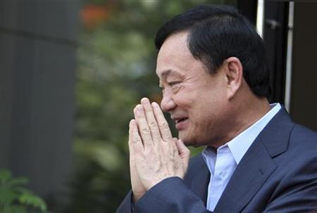 Thailand's former premier Thaksin Shinawatra greets journalists outside his home in Dubai, after Puea Thai Party's Yingluck Shinawatra announced her coalition in Bangkok July 4, 2011. REUTERS/Jumana El Heloueh