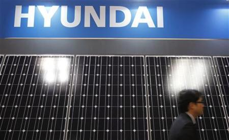 A man walks past solar panel displays by South Korea's Hyundai Heavy Industries at the International Photovoltaic Power Generation (PV) Expo in Tokyo March 2, 2011. REUTERS/Yuriko Nakao