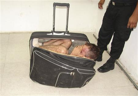 Prison guards stand around inmate Juan Ramirez as he hides in a suitcase during an escape attempt from a prison in Chetumal, July 2, 2011. REUTERS/Government of Quintana Roo-Secretary of State for Public Security
