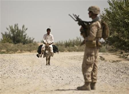 A man rides a donkey towards a U.S. Marine of Weapons Company, 1st Battalion, 3rd Marines, standing at a check point outside Patrol Base Johnson in Helmand province, southern Afghanistan, July 6, 2011. REUTERS/Shamil Zhumatov