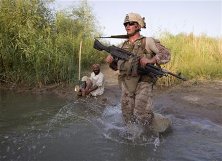 John Mobley, U.S. Marines Lance Corporal of the Weapons Company, 1st Battalion, 3rd Marines walks across a irrigation canal next to an Afghan farmer during a joint patrol with Afghan National Army (ANA) soldiers near the Camp Gorgak in Helmand province, southern Afghanistan, July 3, 2011. REUTERS/Shamil Zhumatov