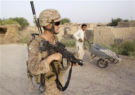 An Afghan boy looks at Kenneth Reynolds, U.S. Marines Corporal of Weapons Company, 1st Battalion, 3rd Marines, during a patrol outside Patrol Base Johnson in Helmand province, southern Afghanistan, July 5, 2011. REUTERS/Shamil Zhumatov