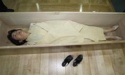 "<p>A woman, donning a traditional yellow hemp robe, lies down in a coffin during a ""well-dying"" course, run by a local district office in Seoul July 4, 2011. REUTERS/Truth Leem</p>"