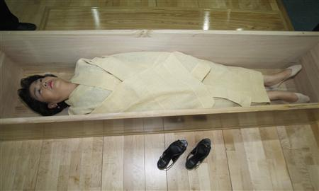 "A woman, donning a traditional yellow hemp robe, lies down in a coffin during a ''well-dying"" course, run by a local district office in Seoul July 4, 2011. REUTERS/Truth Leem"