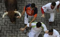 <p>A Cebada Gago fighting bull's horn touches the hand of a runner during the second running of the bulls of the San Fermin festival in Pamplona July 8, 2011. REUTERS/Eloy Alonso</p>