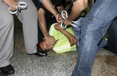 Plainclothes policemen detain a supporter of the ''Bersih'' (Clean) electoral reform coalition during a rally in Kuala Lumpur July 9, 2011. REUTERS/Ashraf Shamsul Azlan
