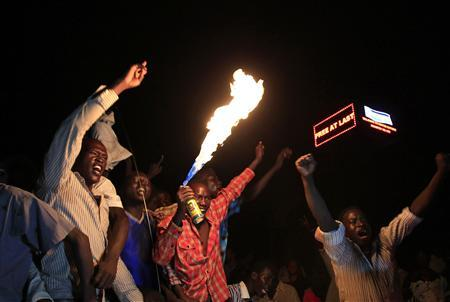 People take part in South Sudan's independence day celebrations near the countdown clock in Juba July 9, 2011. REUTERS/Thomas Mukoya