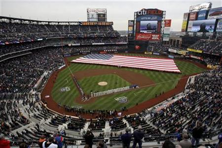 A flag is stretched across the field for the national anthem before the start of the New York Mets home opener against the Washington Nationals National League game in MLB baseball action at Citi Field in New York April 8, 2011. REUTERS/Jessica Rinaldi