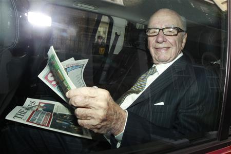 News Corporation CEO Rupert Murdoch holds a copy of The Sun and The Times as he is driven away from his flat in central London, July 11, 2011. REUTERS/Luke MacGregor