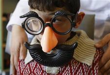 <p>An autistic child wears a toy mask plays at the Consulting Centre for Autism in Amman, March 30, 2010. REUTERS/Ali Jarekji</p>