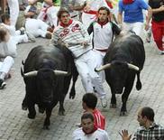 <p>Un corredor queda atrapado entre dos toros de Victoriano del Río en la entrada a una plaza de toros durante el sexto encierro en San Fermín, en Pamplona REUTERS/Joseba Etxaburu</p>