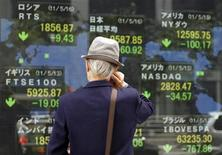 <p>A man looks at an electronic board displaying various market indices from around the world outside a brokerage in Tokyo May 16, 2011. REUTERS/Toru Hanai</p>