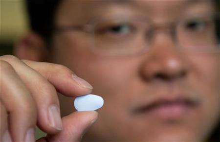 Dr. Albert Liu, director of HIV Prevention Intervention Studies at San Francisco's Department of Public Health, holds a study pill for his Project T study in San Francisco, California, August 8, 2006. REUTERS/Kimberly White