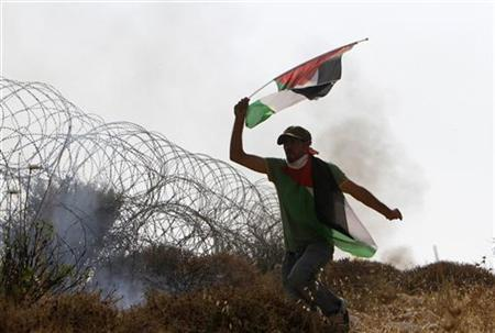 A protester waves a Palestinian flag as he runs near a section of the Israeli barrier fence during a rally by Palestinian and foreign activists near Qalandiya, close to the West Bank city of Ramallah, July 9, 2011. REUTERS/Mohamad Torokman