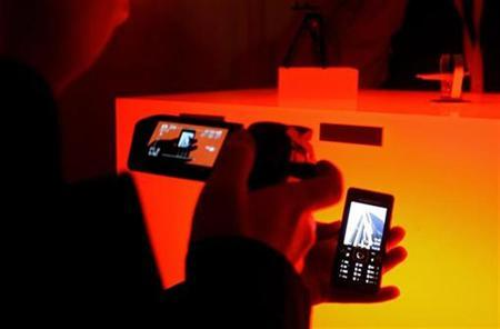 A man takes a picture using the Sony Ericsson C903 Cyber-shot mobile phone during the Mobile World Congress in Barcelona February 15, 2009. REUTERS/Gustau Nacarino