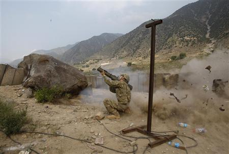 US army Private First Class Seng Thor from 2nd Platoon, Charlie company, 2nd battalion, 27th Infantry Regiment fires a Law rocket launcher at a suspected Taliban position near Check point two point five in Kunar province, Afghanistan, July 14, 2011. REUTERS/Baz Ratner