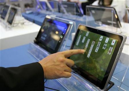 A visitor plays with a tablet PC at the Intel booth during the Computex 2011 computer fair at the TWTC Nangang exhibition hall in Taipei May 31, 2011. REUTERS/Pichi Chuang