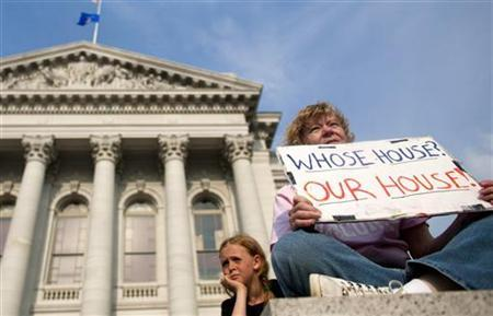A protester holds a sign as they return to occupy the state Capitol, while the Wisconsin State Assembly takes up the budget bill that was proposed from Wisconsin Republican Governor Scott Walker, in Madison June 14, 2011. REUTERS/Darren Hauck
