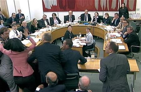 Wendi Deng (2nd L) lunges towards a man trying to attack her husband, News Corp Chief Executive and Chairman Rupert Murdoch, during a parliamentary committee hearing on phone hacking at Portcullis House in London July 19, 2011. REUTERS/Parbul TV via Reuters Tv