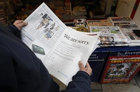 A newspaper vendor poses with a copy of The Times, featuring an apology from News Corp chairman and chief executive officer Rupert Murdoch at a news stand in London July 16, 2011. REUTERS/Suzanne Plunkett