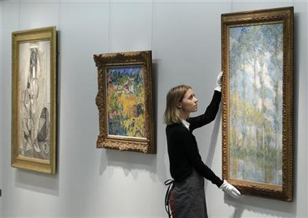 A Christie's employee poses with artist Claude Monet's ''Les Peupliers'' at Christie's auction house in London April 15, 2011. REUTERS/Luke MacGregor