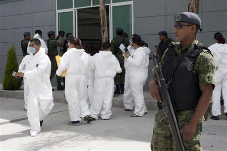 A soldier stands guard as members of a forensic team, in chemical protective clothing, prepare to enter a warehouse used to store chemicals for illicit drug processing at an industrial park in Queretaro July 20, 2011. REUTERS/Demian Chavez