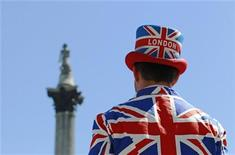 <p>A street performer wearing a Union flag suit and top hat stands in front of Nelson's Column at Trafalgar Square in London June 26, 2011. REUTERS/Luke MacGregor</p>
