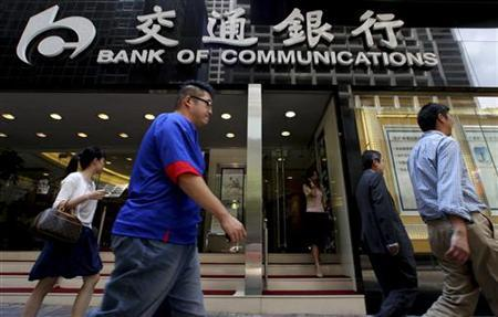 People walk past the Bank of Communications at its central branch in the financial district of Hong Kong August 19, 2009. REUTERS/Aaron Tam