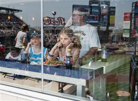 The stadium is reflected in the glass as young fans sit in an air-conditioned restaurant and watch the New York Mets play the St. Louis Cardinals in the first inning of their MLB National League baseball game at CitiField in New York, July 21, 2011. REUTERS/Ray Stubblebine