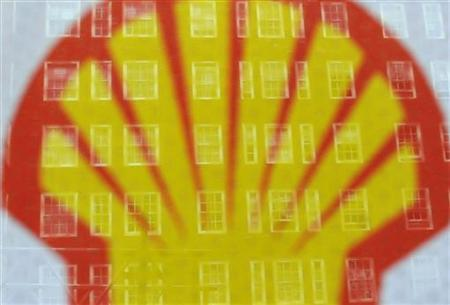 Apartment windows are seen behind a logo at a Shell petrol station in central London July 29, 2010. REUTERS/Toby Melville