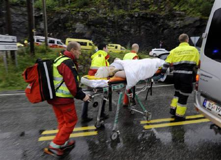 Rescue personnel push an injured victim away from the camp site in Utoeya July 23, 2011. REUTERS/Morten Edvardsen/Scanpix