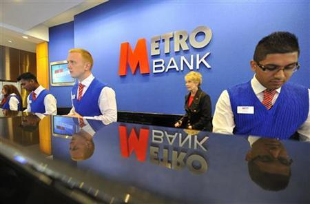 Staff serve customers at the first branch of Metro Bank in Holborn in central London July 29, 2010. REUTERS/Toby Melville